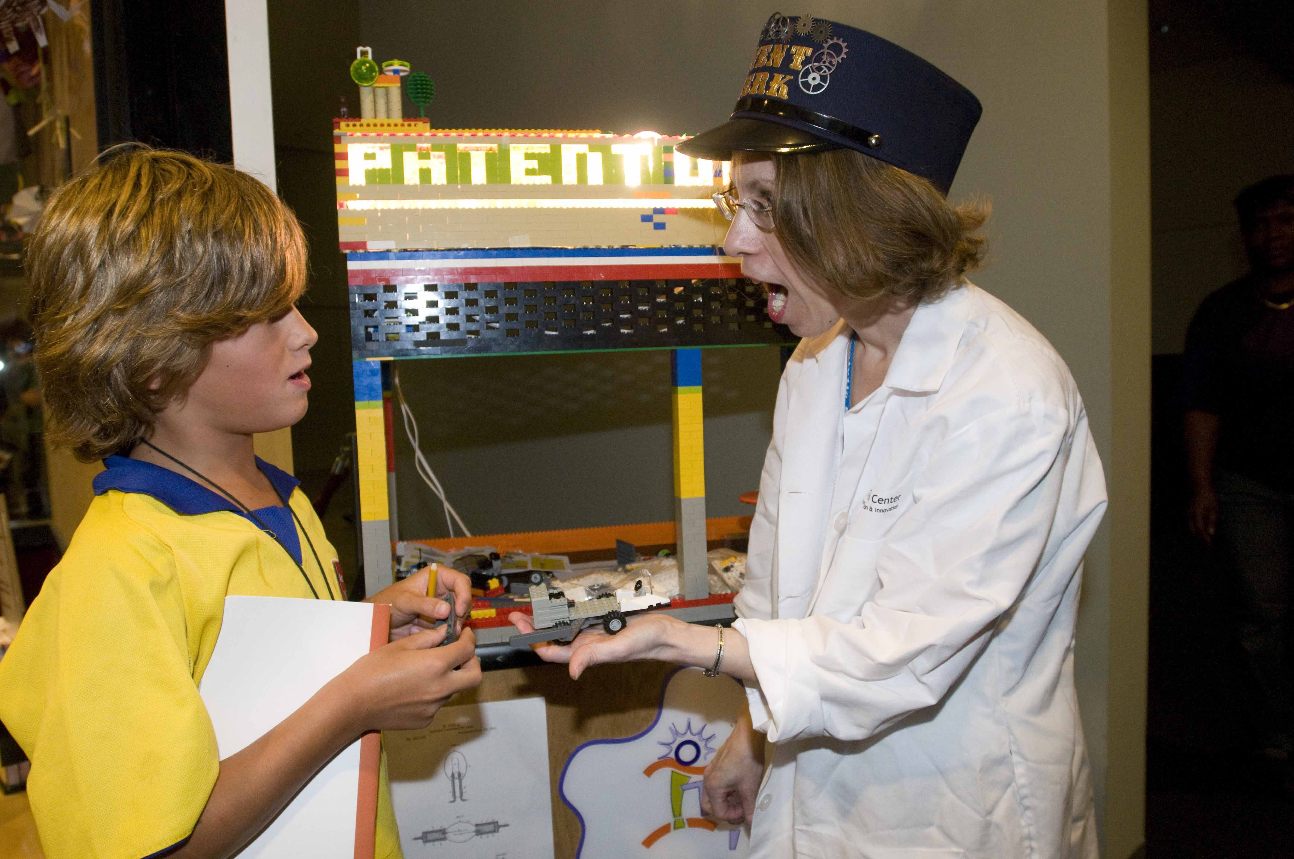 A boy takes his invention to Spark!Lab's Patent Office.