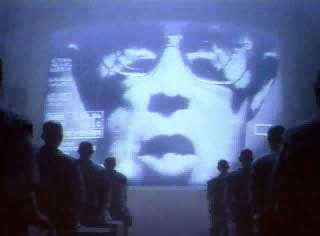 "Scene from Apple's ""1984"" Super Bowl advertisement: large, projected talking head."
