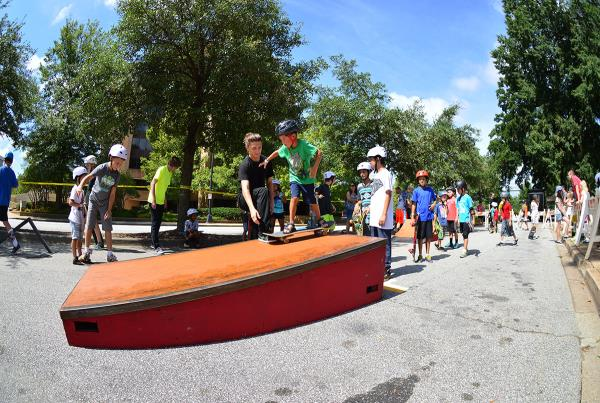 Pros teaching kids how to skateboard at Innoskate's clinic.