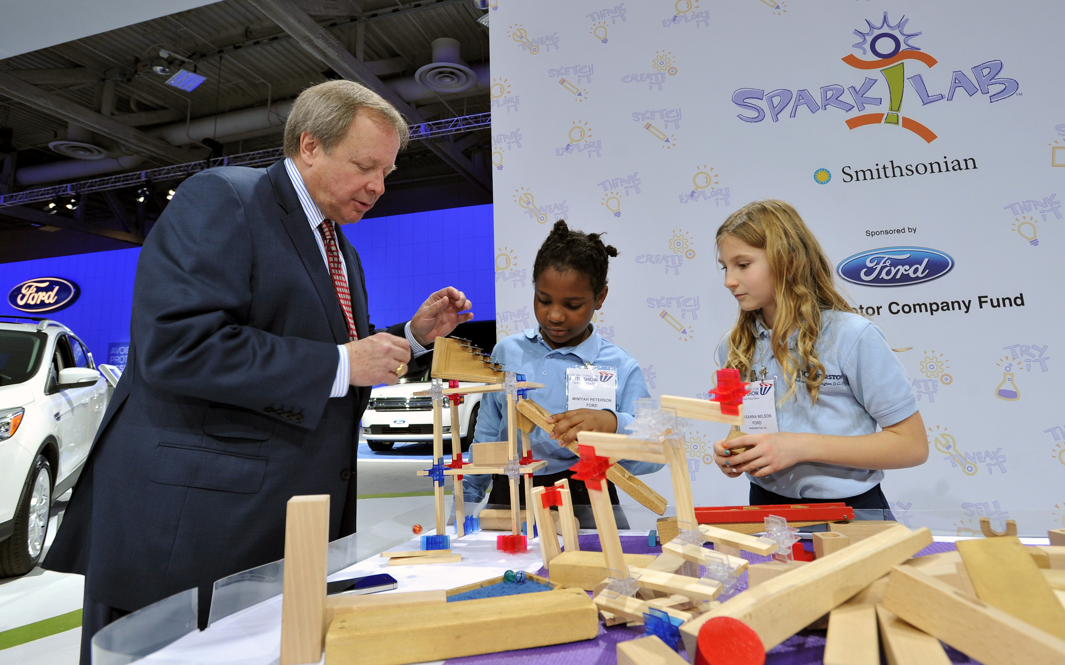 Edsel Ford II joins fourth grade students Miniyah Peterson (center) and Raeanna Nelson (right) from the Cornerstone Schools of Washington, DC, in a Smithsonian Spark!Lab activity creating a sound pathway for marbles.