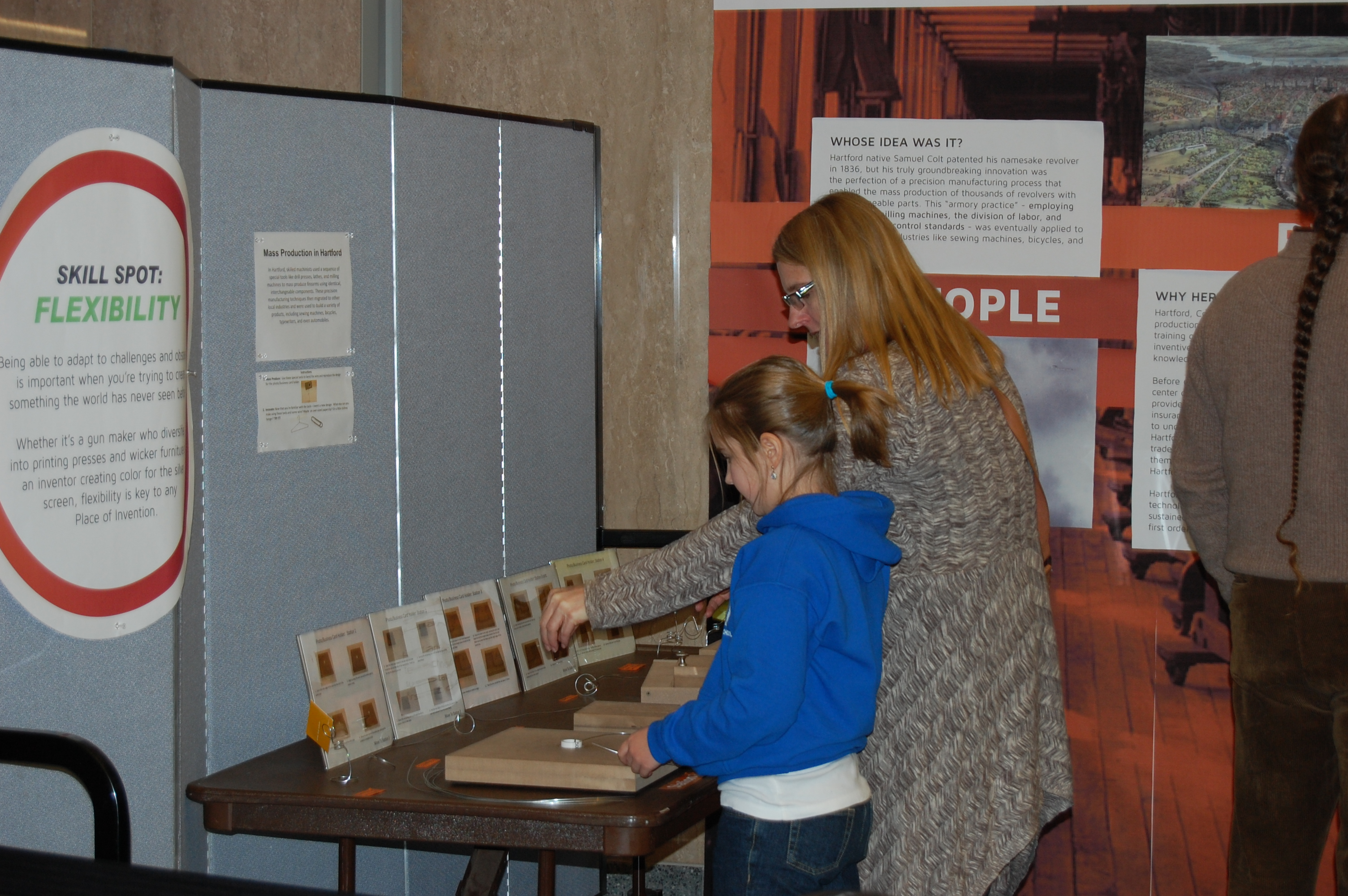 Visitors testing an interactive where they are asked to use a jig to twist wire into a business card holder.