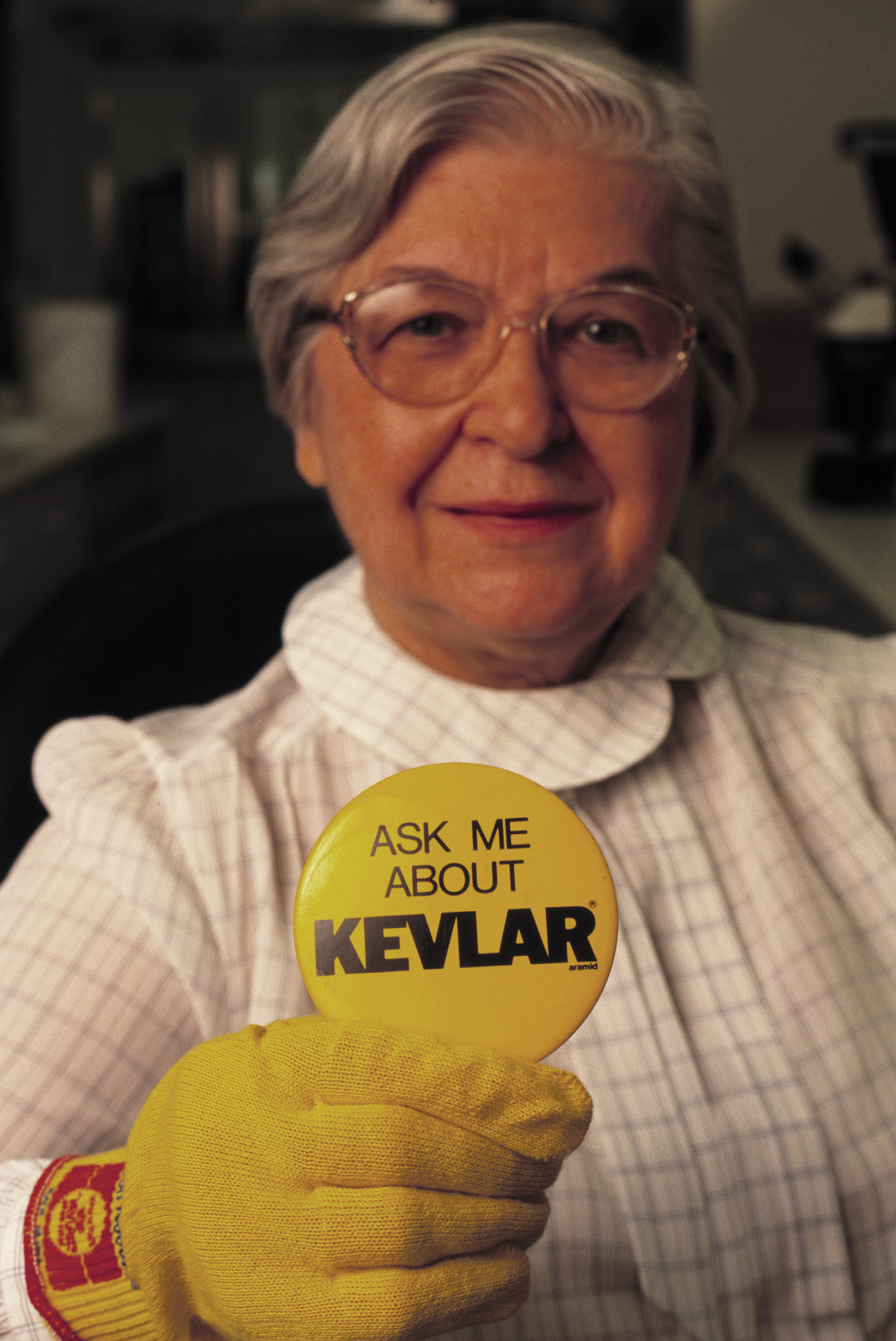 "Inventor Stephanie Kwolek wearing yellow Kevlar glove and holding up yellow button that reads ""Ask Me About Kevlar."""