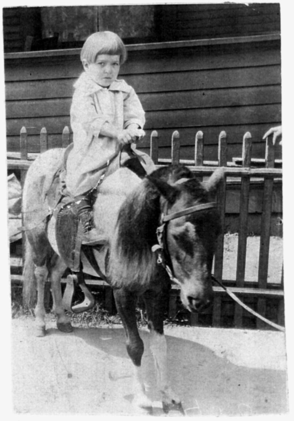 Kwolek at age three sitting on a small horse in a black and white photo.