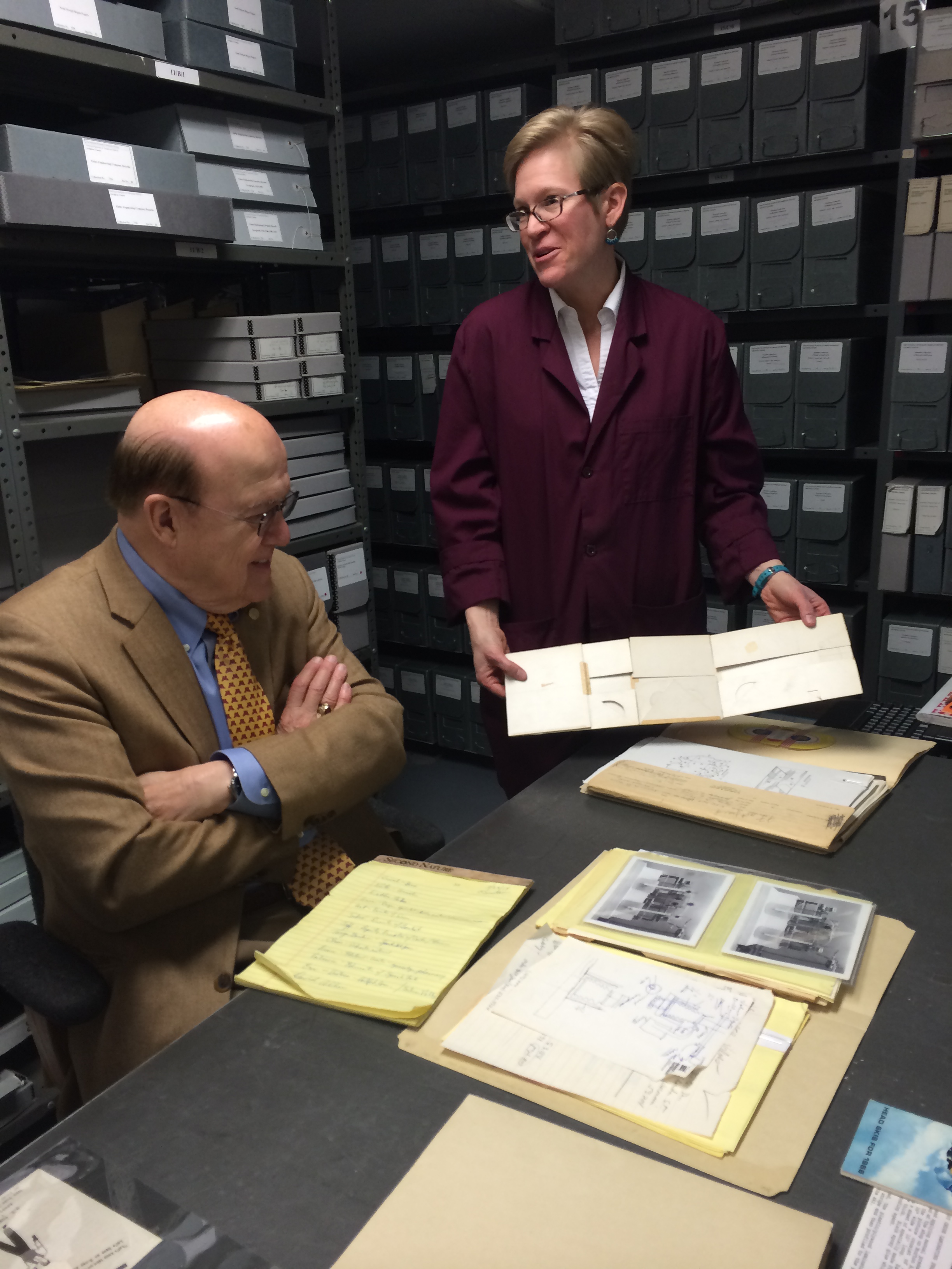 Archivist Alison Oswald shows Manny Villafana archival documents.
