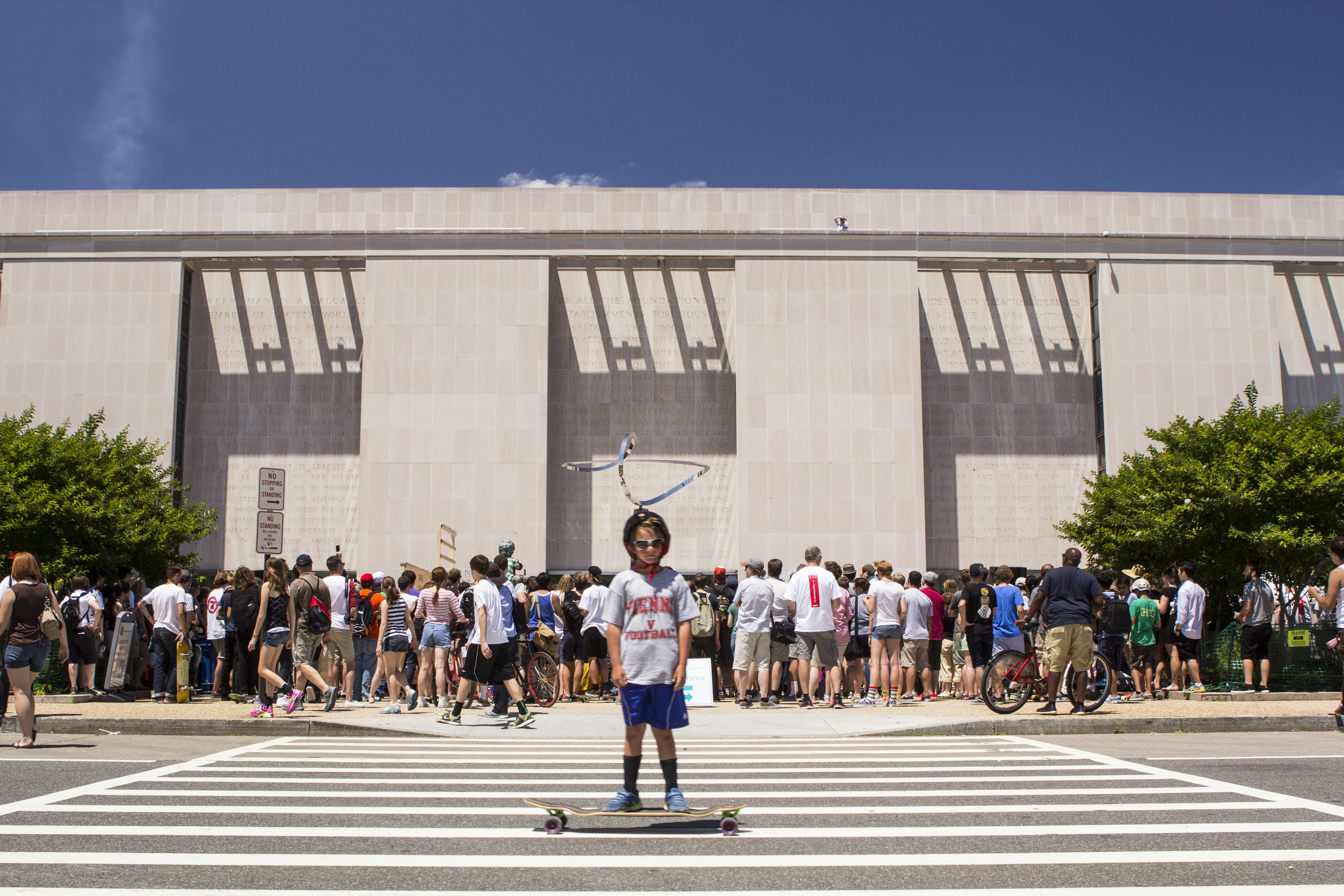 A young boy skateboards in front of the National Museum of American History.
