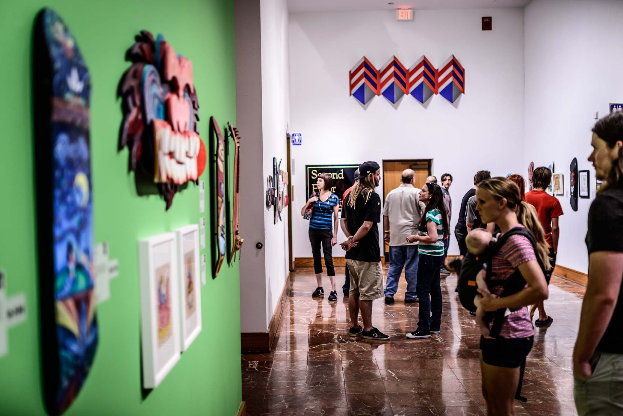 "Visitors browse the ""All Decked Out"" skateboard art exhibit."