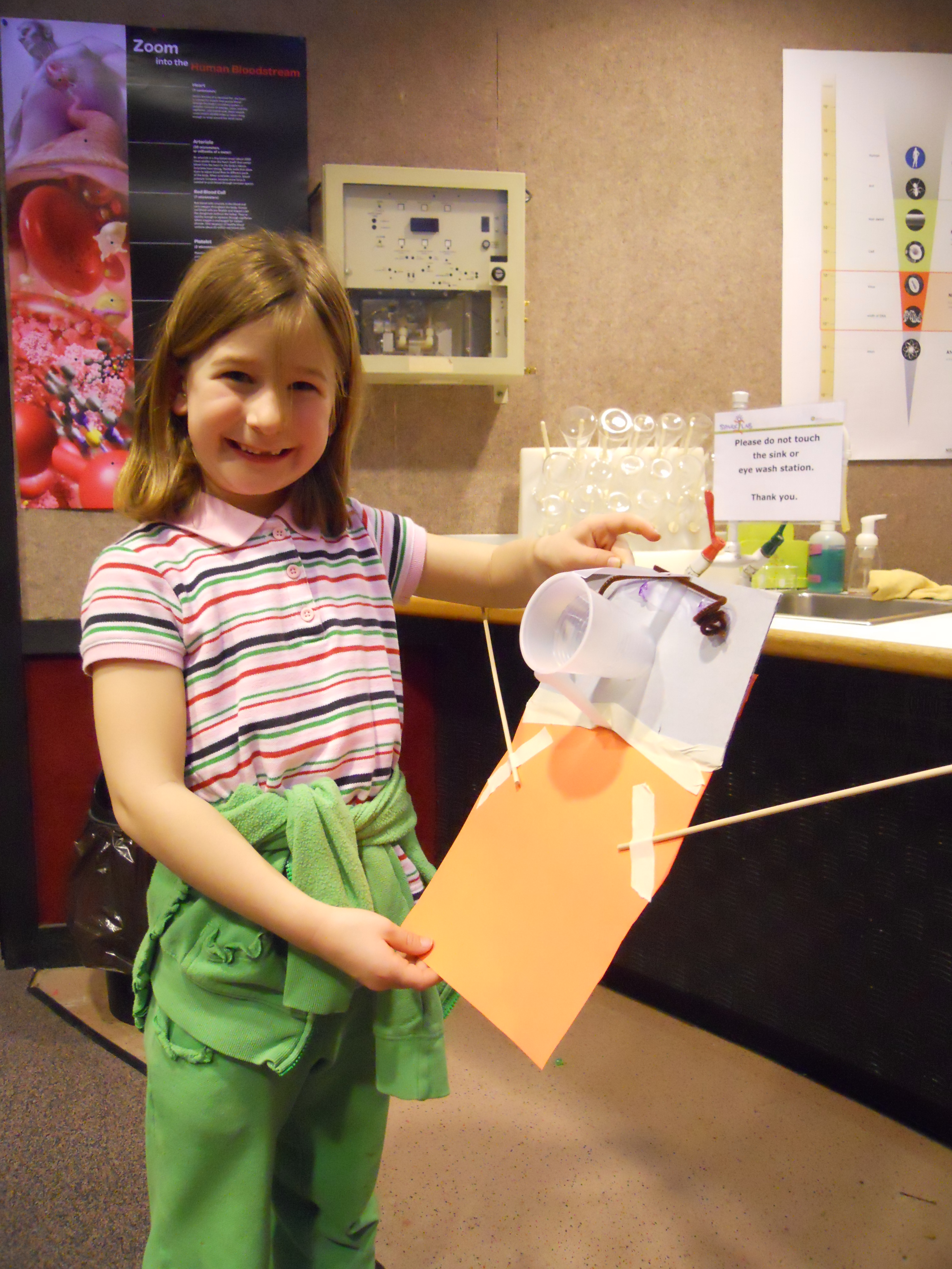 "A girl holds up her paper ""robot"" made in Spark!Lab during NanoDays."