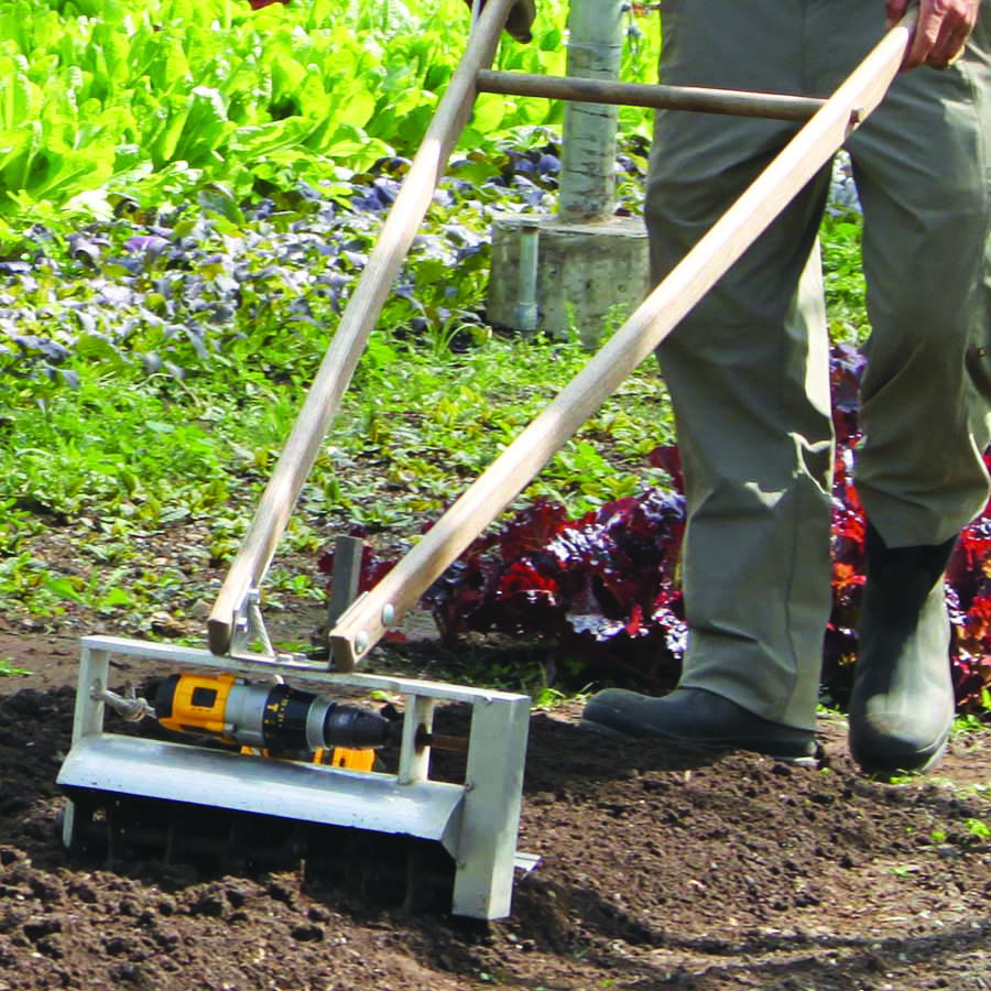 Eliot Coleman prepares a bed in the garden using his invention, the Tilther, to mix compost into the soil.