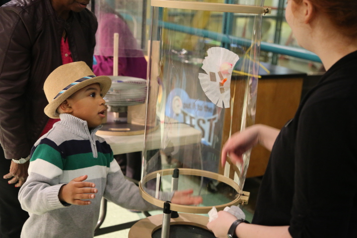A young visitor tests his flying invention in the Vertical Wind Tunnel