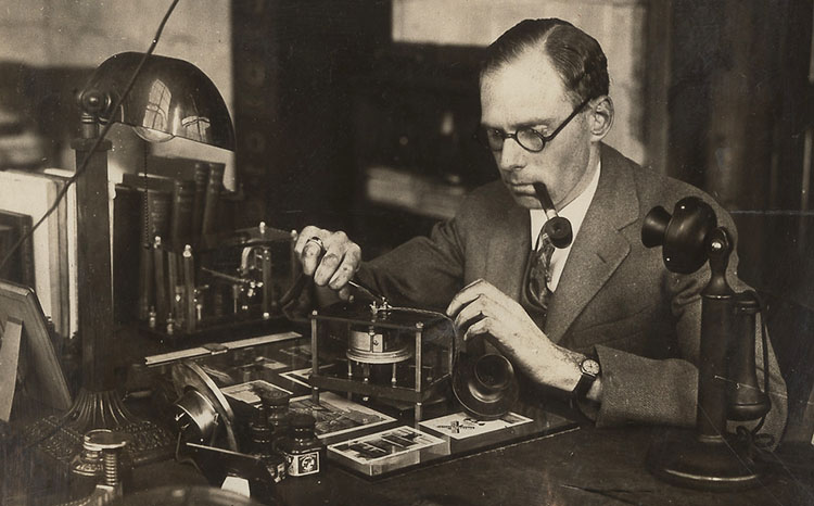 Charles Adler, in suit and tie, working on an unidentified device at his desk