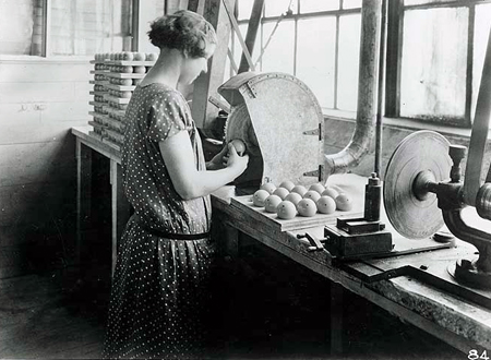 Woman buffing Celluloid billiard ball during manufacturing process