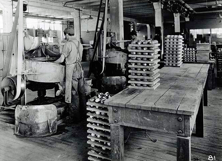 Man grinding Celluloid billiard balls with water and a fine abrasive during manufacturing process