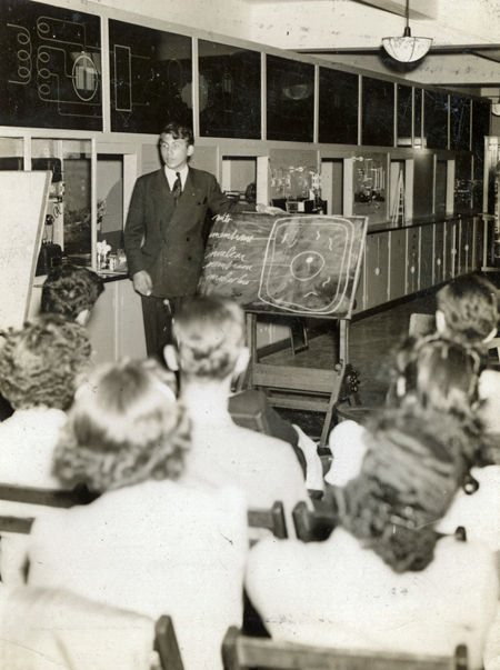 A young Joshua Lederberg stands at a blackboard on an easel while lecturing to a classroom of fellow students.
