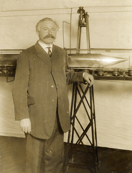 Emile Bachelet standing next to his model prototype for a maglev train