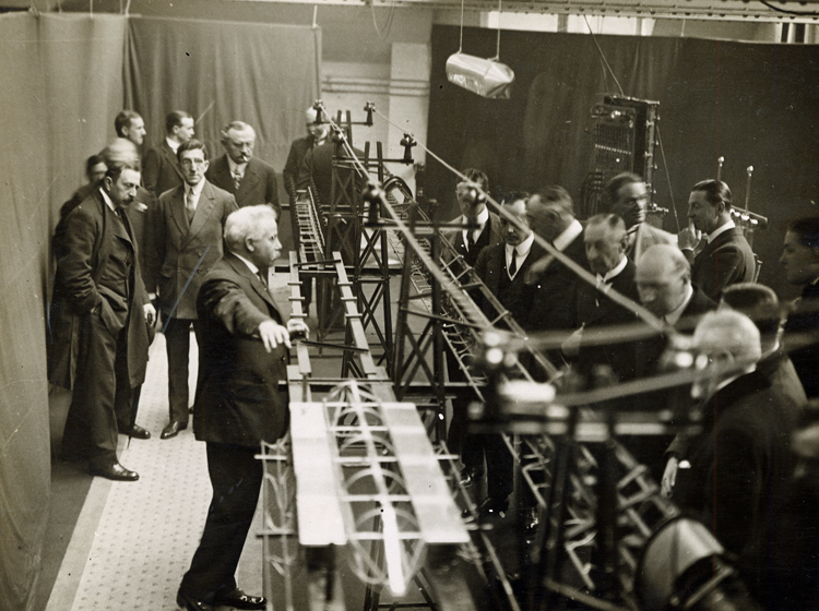 Emile Bachelet demonstrating his maglev train prototype to a group of people in London, 1914