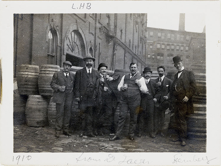 """Seven men in suits standing for a photo in from of wooden barrels. In pencil under the photo is written: """"From Dr. Jaeger"""""""