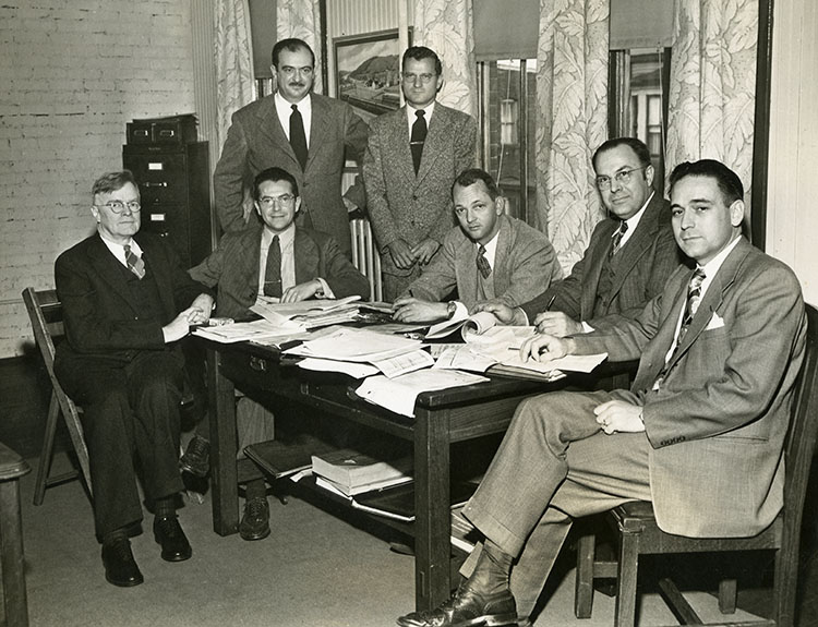 Group of 7 men in suits seated around a conference table