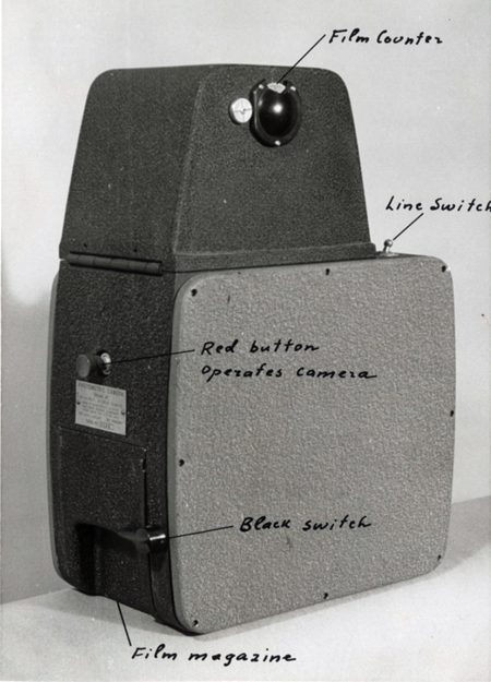 Black-and-white photo of a metal photometric camera with handwriting pointing out specific features: film counter, line switch, red button operates camera, black switch, film magazine.