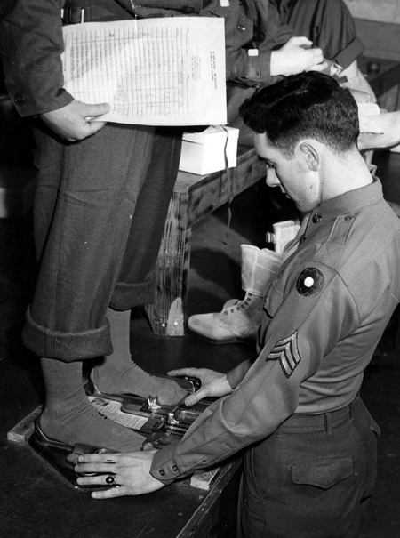 A young Army sergeant wearing his insignia and a 9th Infantry Division patch on his left arm measures another soldier's feet, using a double Brannock device to measure both feet at once.