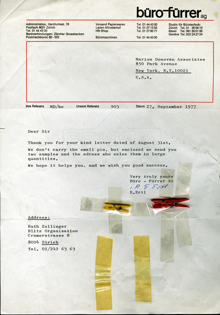 A typewritten letter, dated 27 September 1977, from Büro-Fürrer AG in Switzerland to Marion O'Brien Donovan, in response to Donovan's inquiry about a source for small clothespins to use with her closet organizer. Two clothespins are taped to the letter; one is yellow and about 1 inch long, the other is red and about 1.5 inches long.