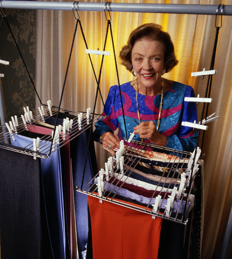 Marion O'Brien Donovan smiles at the camera. She is standing behind 2 Big Hang-Up organizers and is placing a clothespin on one garment to attach it to the rack. A backlit beige curtain is behind her and the organizers hang from a horizontal metal pole. A few clothespins are attached to the cords that suspend the organizer from the pole.