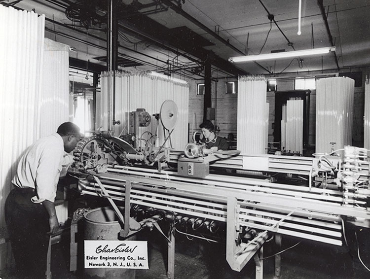 A man and a woman inspecting or making long glass tubes