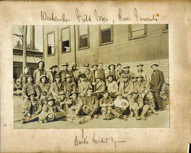 Posed group photo of about 30 tunnel workers