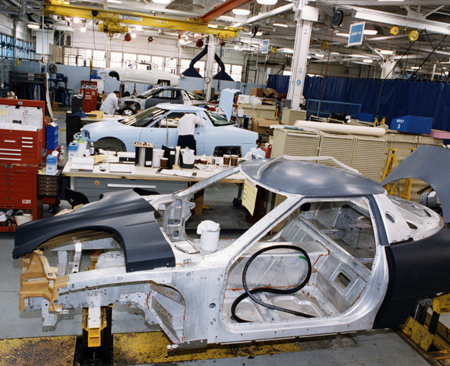 EV1 prototype under assembly, 1994. A partial chassis is in the foreground with a car having its outer body assembled is in the mid-ground.