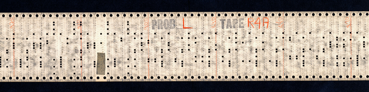 "A long strip of paper, about 3 inches wide. The upper and lower edges have regular rows of perforations. The center of the tape has punch holes carrying the program code. The words ""Prob L"" and ""Tape R4A"" are stamped at the top of the strip, and regularly-spaced red vertical lines have been drawn across the tape and numbered 870, 880, 890, 900, 910, and 920."