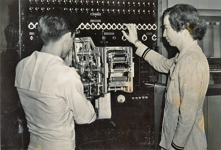 A young navy ensign stands with his back mostly to the camera and next to Grace Hopper, wearing her navy uniform and standing in profile to the camera. She has her right hand on one of the many dials that run across the top of the Mark I computer. She and the ensign are looking at a section of the computer with many gears to move the punched tape code through the machine.