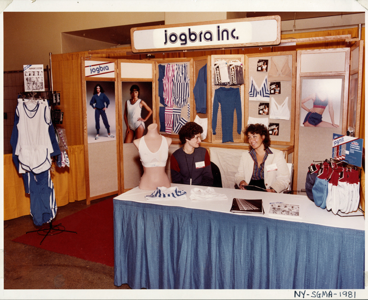 Hinda Miller (left) and Lisa Lindahl sit at a skirted trade show table in 1981. The 2 women are looking at each other and smiling. A half-torso mannequin is on the table, modeling a Jogbra. Other Jogbra Inc. merchandise, including gloves, track suits, bras, shorts, and one-piece running outfits, is displayed on the table and behind them on the booth walls, along with large photographs of women wearing some of the gear.