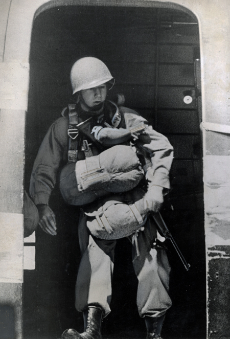 A paratrooper, carrying full gear and a gun and wearing a helmet, stands at the open hatch with a pigeon attached to his chest. The pigeon wears a specially-designed vest to protect it when the paratrooper jumps from the plane.