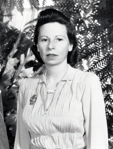 Enid Bissett standing in front of greenery