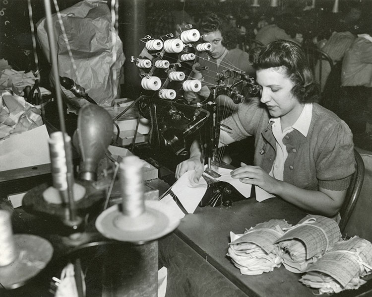 Woman working at sewing machine that has several bobbins of thread