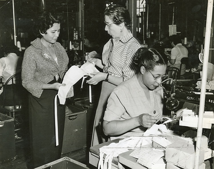 Two women inspecting a bra while a third sews