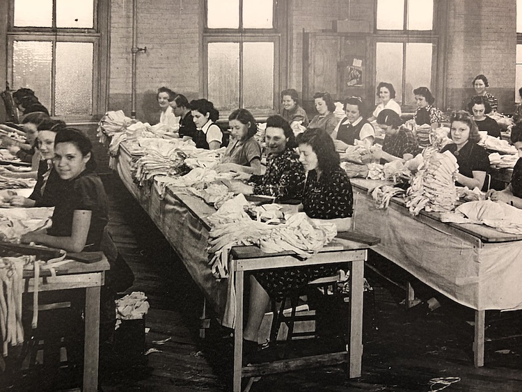 Dozens of women sitting at long tables working on bras
