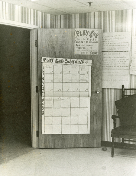 Hand-drawn calendar on the back of door, titled Play Lab Schedule and stating All Welcome