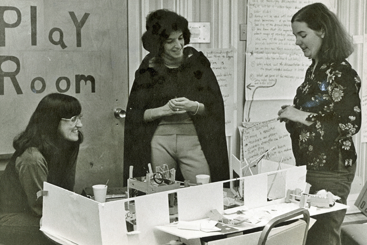 Elaine Ostroff, on left, with two other women, looking at a model of a play space. The words Play Room are on the door behind Ostroff.