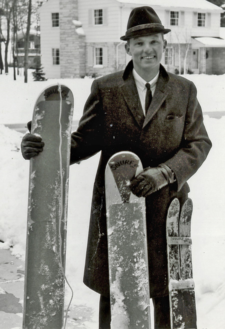 Poppen, standing outside in the snow, holding 3 Snurfer prototypes