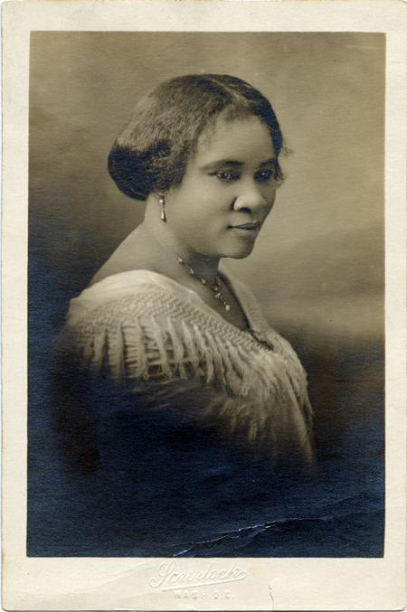 A sepia-toned 3/4 profile studio portrait photograph of Sarah Breedlove Walker, known as Madam C. J. Walker. She is wearing a shawl with tassels adorning the neckline, fastened with a brooch, and she wears drop earrings with matching necklace and a brooch.