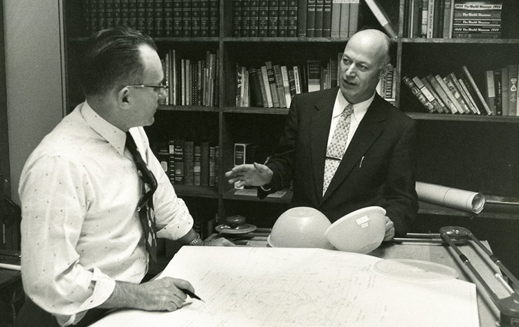 A man wearing glasses holds a pen over a blueprint drawing while Earl Tupper gestures with 2 Tupperware bowls