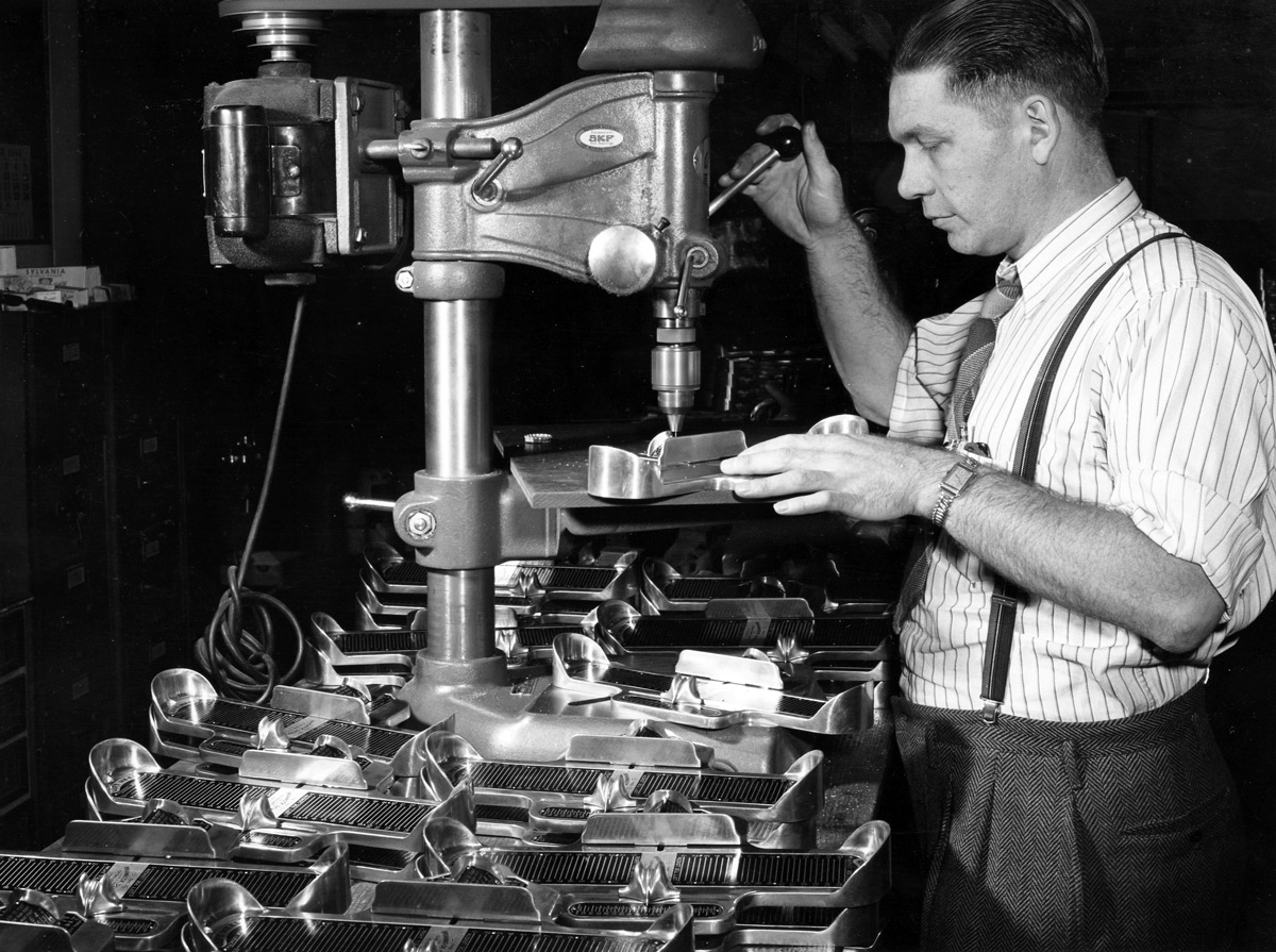 Image of a worker using a drill press at the Brannock Device Company