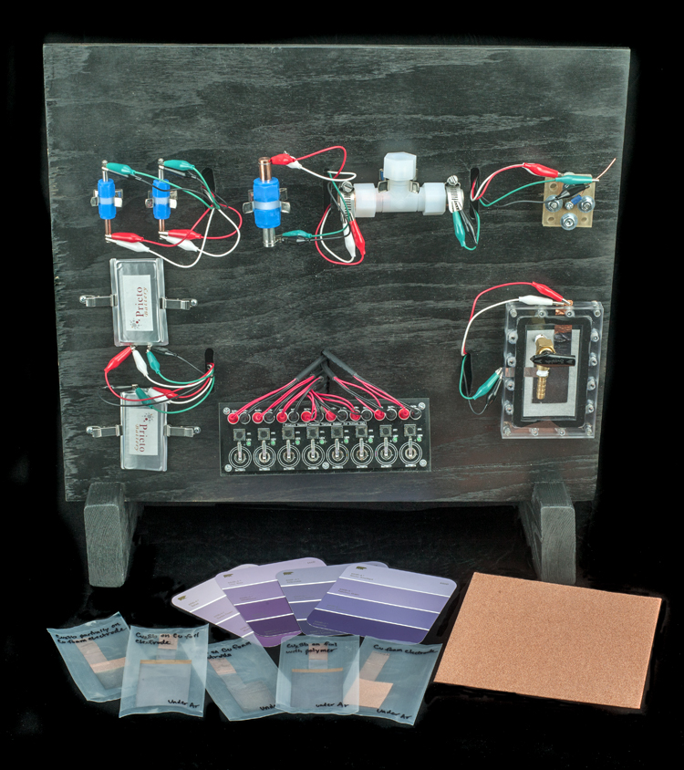 Components of prototype Prieto batteries, 2014. A wooden board holds several different types of cells for testing.