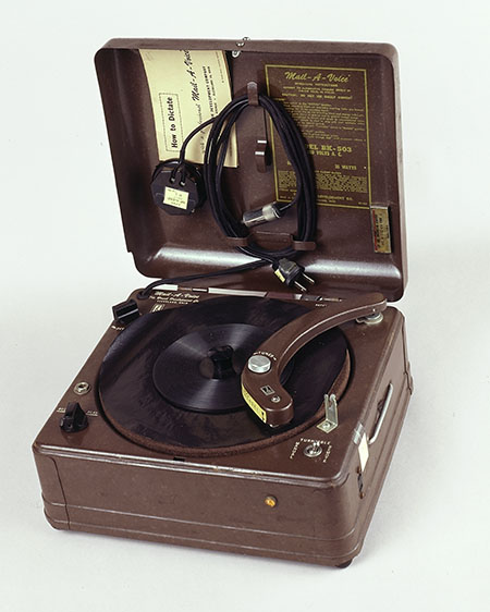 A square machine with a lid. It looks like an old-fashioned record player.