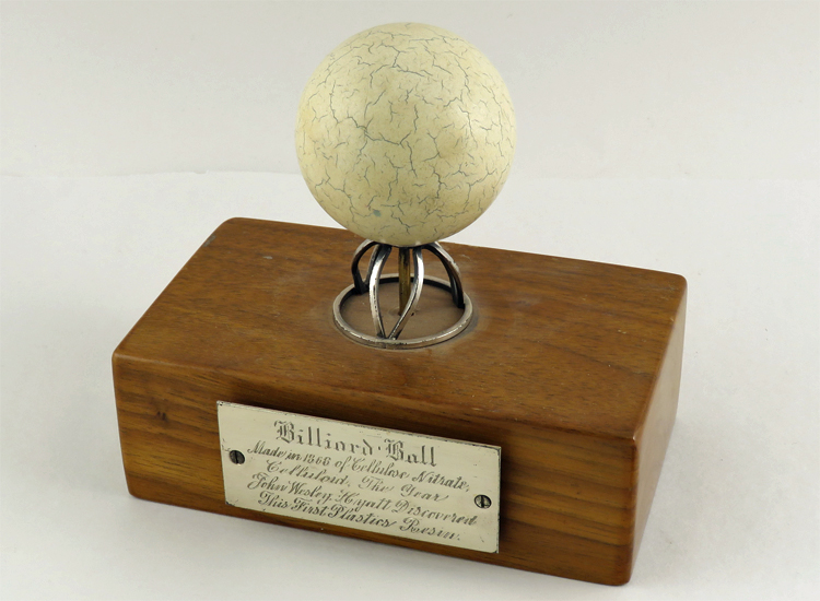 Celluloid billiard ball mounted on ceremonial stand, with brass plaque identifying John Wesley Hyatt as the inventor of celluloid.