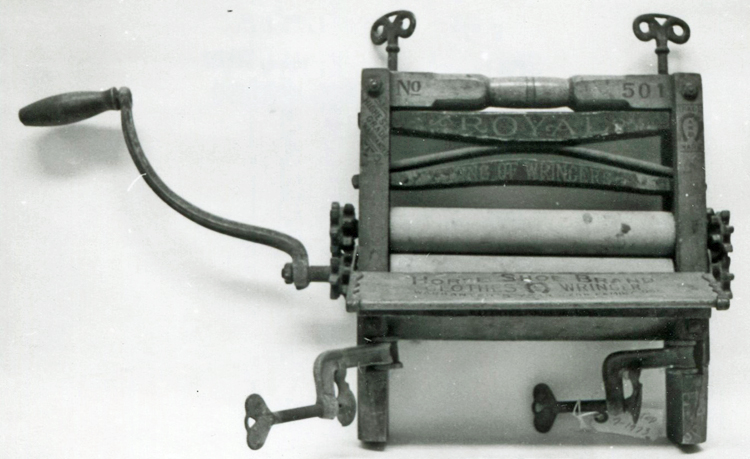 Black-and-white photo of a clothes wringer, comprised of two rubber rollers in a wood frame with metal gears, clamps, etc.