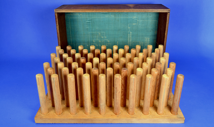 Wooden box with the lid off, showing 40 spindles and a blueprint lining the lid.