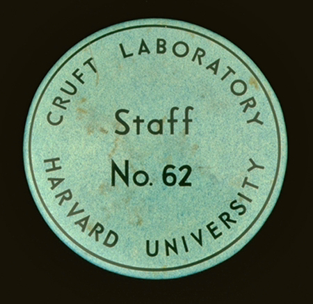 "A round green metal badge, about 1.5 inches in diameter. The words ""Cruft Laboratory Harvard University"" are printed around the outer edge, and the words ""Staff No. 62"" are printed in the center of the badge."