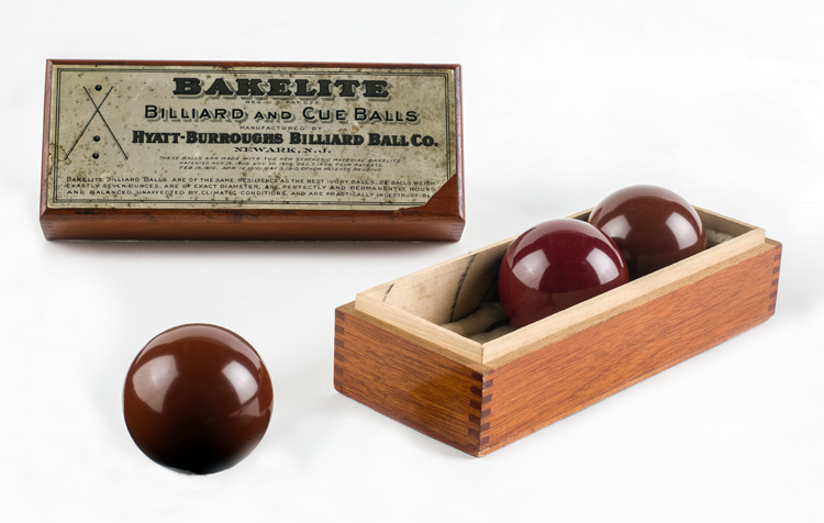 3 reddish-brown Bakelite billiard balls in a wooden box labeled with Hyatt-Burroughs Billiard Ball Co. name