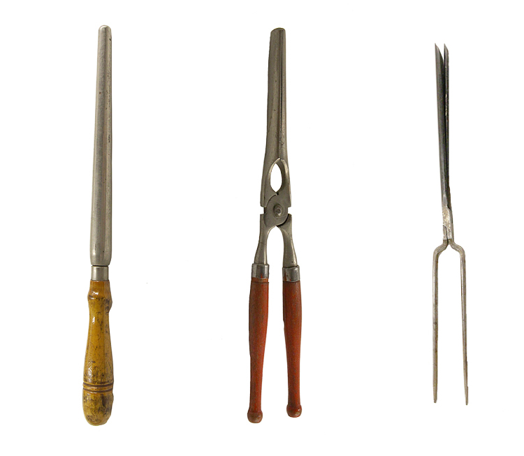 3 hairstyling instruments in a row. A metal permanent rod with a wooden handle is at the left. A metal straightening iron with two hinged tongs and wooden handles is in the center. An all-metal curling iron with 2 narrow tine-like handles and 2 tweezer-shaped tongs is at the right.